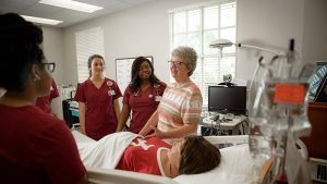Nursing students stand around a hospital bed listening to an instructor.